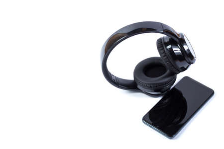 Black smartphone and wireless headphones isolated on a white with copyspace. Banque d'images