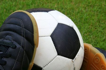 wornout: A worn-out soccer ball with a pair of futsal shoes on grass.