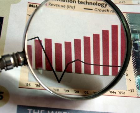 Una lente di ingrandimento concentrandosi su un grafico nel business sezione del giornale.