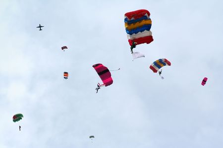 showmanship: A group of skydivers parachuting their way down.