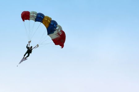 showmanship: A skydiver parachuting down from the sky.