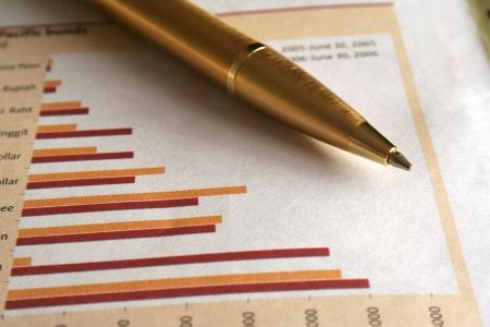 Un oro penna a sfera sul business pagina del giornale.