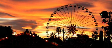 Panorama van een carnaval aftekenen tegen de avond skyline bij zonsondergang.