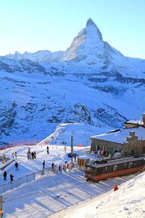 The train station in Gornergrat, at the Swiss Alps with the Matterhorn in the background as the sun begins to set.