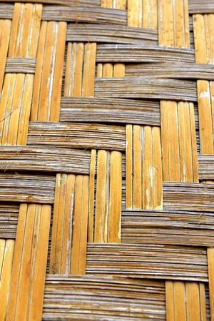 Interwoven rattan strips forming the walls of a traditional Malay house.