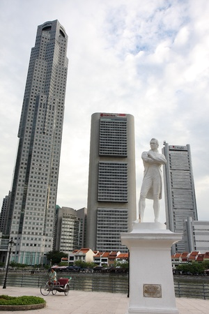 SINGAPORE - AUGUST 21, 2010: The statue of Sir Stamford Raffles (the founder of Singapore) at the site where he first landed in the island in the year 1819, against the backdrop of modern skyscrapers and an old trishaw, on August 21, 2010 in Singapore. Th
