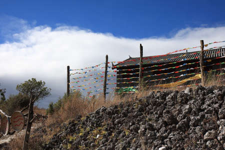Colorful Tibetan prayer flags fluttering in the wind at the Naxi tribal village at Dongba Valley in Lijiang, Yunnan Province of China