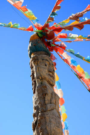 Naxi tribe totem pole attached with colorful Tibetan prayer flags in Dongba Valley, Lijiang, Yunnan Province of China