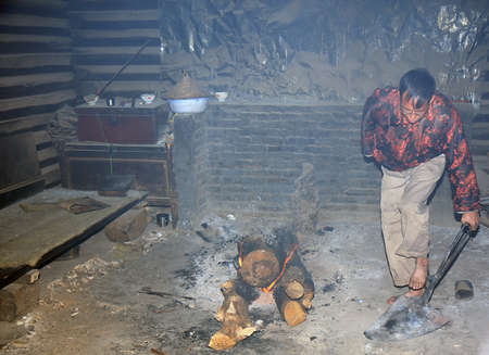 LIJIANG, CHINA - DECEMBER 8, 2010: An unidentified Naxi ethnic man handles a hot metal plate for the tongue burning ritual at the Dongba Valley Cultural Village, on December 8, 2010 in Lijiang, Yunnan Province of China. This is a special skill in the trad
