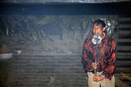 LIJIANG, CHINA - DECEMBER 8, 2010: An unidentified Naxi ethnic man presses a hot metal plate onto his tongue at the Dongba Valley Cultural Village, on December 8, 2010 in Lijiang, Yunnan Province of China. This is a special skill in the tradition of the N