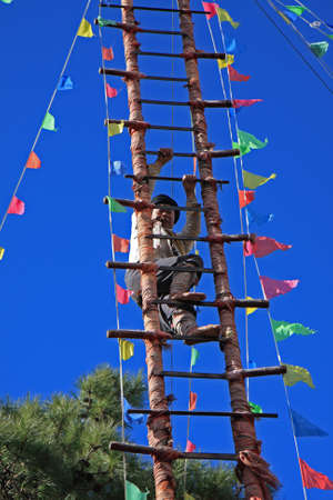 LIJIANG, CHINA - DECEMBER 8, 2010: An unidentified barefooted Naxi ethnic man climbs the steps of a ladder made of sharp knives at the Dongba Valley Cultural Village, on December 8, 2010 in Lijiang, Yunnan Province of China. This is a ritualistic custom o