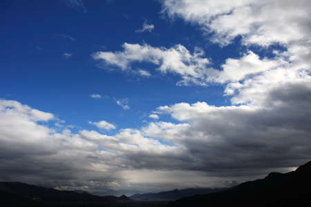 White clouds against blue sky over the hilly terrain of Dongba Valley in Lijiang, Yunnan Province of China  Stock Photo