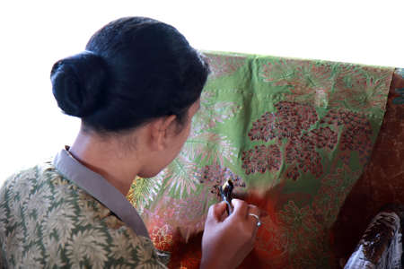 BALI, INDONESIA - AUGUST 26, 2011  An unidentified Balinese woman applies dye on a piece of batik cloth, on August 26, 2011 in Bali, Indonesia  Batik-making is an important part of Indonesian culture