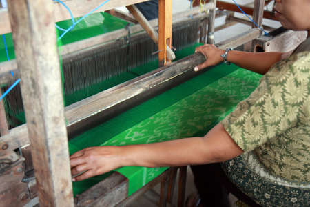 BALI, INDONESIA - AUGUST 26, 2011  An unidentified Balinese woman operates a manual weaving contraption to knit batik cloth, on August 26, 2011 in Bali, Indonesia  Batik-making is an important part of Indonesian culture