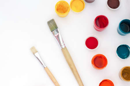 Paint jars and brushes on white background top view Stock Photo
