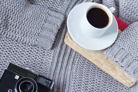 high-angle shot of a white ceramic cup with white coffee, book and an old camera of a pullover