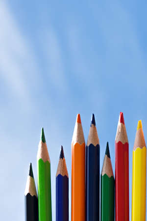 Color pencils isolated on blue sky background