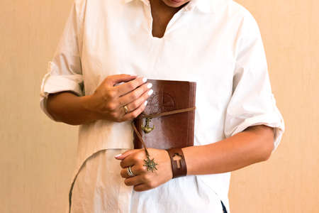 A brown travel journal imprinted with a compass rose in hand Stock Photo