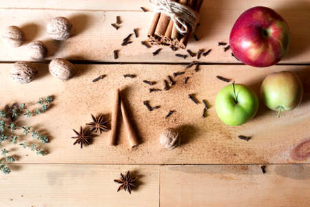 Frame of autumn leaves, chestnuts and ingredients for hot spiced tea and central copy space over rustic table viewed from above. Fall concept
