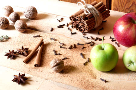 Fresh red and green apples, cinnamon sticks, anise stars, walnuts on wooden background