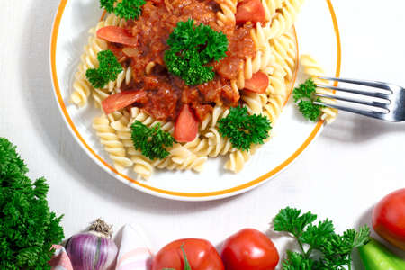 stirred: plate of penne pasta with tomato sauce on white background