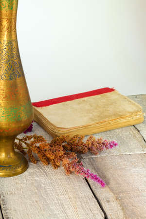 Old book, and dried flower and vase on wooden table. Vintage still life.