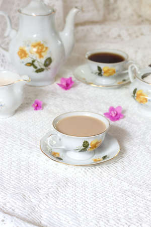 A tea cup decorated with flowers, two biscuits and a candle on a white wooden table. In the background a turquoise clock on a yellow wainscot. Vintage tea time Stock Photo