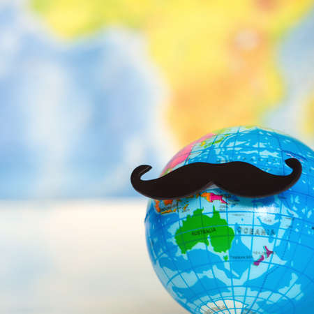 Movember beard word sign world map background.