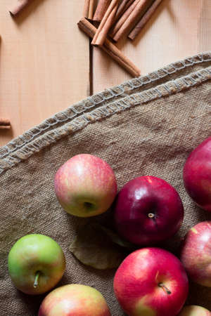 Red apples on a wooden background with sacking. fruit, natural food. Stock Photo