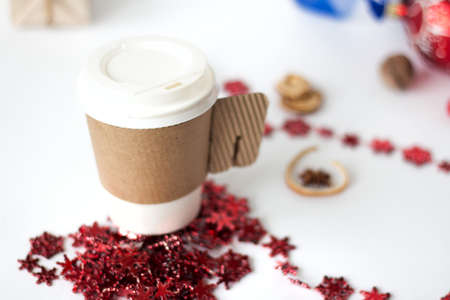 Paper cup of coffee surrounded by Christmas decorations on Christmas decor on white background background