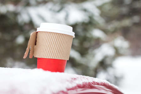 Cup of tea or coffe on snow outdoor. Free space for text.