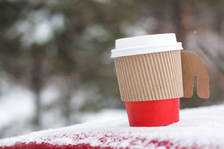 Winter coffee in red paper cup in outdoors with snow