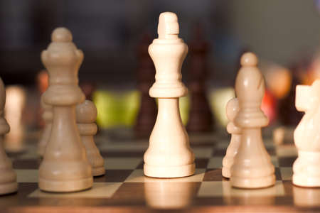 White chess quenn stands out against the background on a chess board