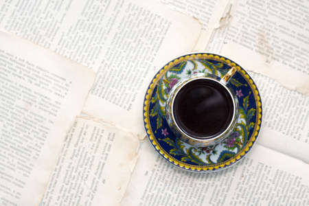 Vintage cup of coffee on old paper sheets or book