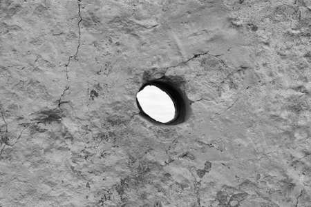 hole in concrete black and white photo