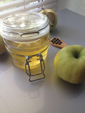 a honey jar and an apple on a light background