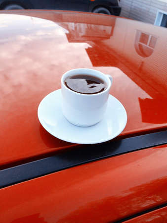 a cup of hot coffee on the background of a red car caravanning concept 版權商用圖片