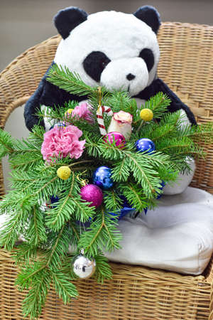 Bouquet of Christmas tree with Christmas decorations and lovely flowers. On a wicker chair. Soft toy bear in the background. The concept of gift and celebration.