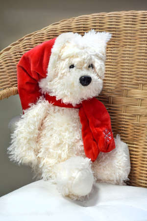 Soft toy polar bear sitting on a wicker chair. The concept of Christmas gift and Christmas holiday.