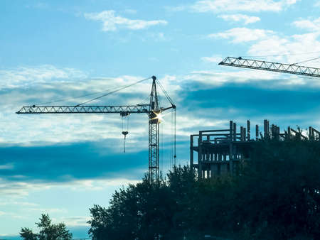 High crane on a construction site against the sunset sky. The concept of a new building for a young family.