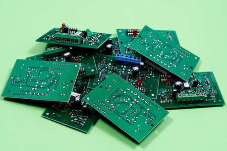 Electronic printed circuit boards on a green background. Recycling of electronic waste and repairing broken appliances.