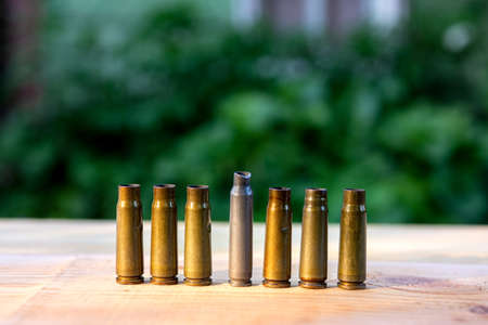 machine gun cartridge cases of different sizes on a wooden background