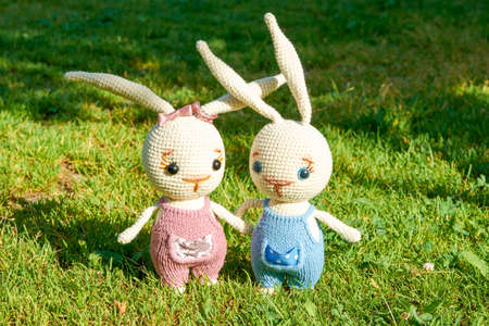 Two toy rabbits on the green grass on a summer day. Background for an Easter picture. Archivio Fotografico
