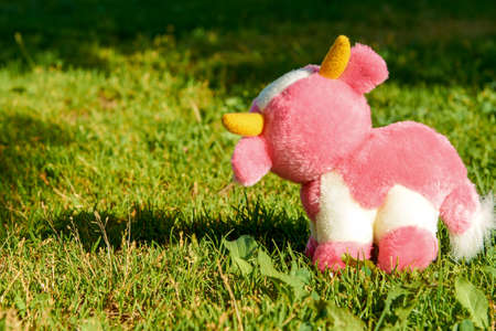 A pink plush cow grazes in a green meadow. A warm Sunny day.