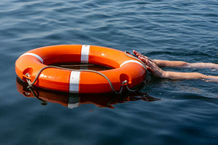 The man's hands reach for the lifebuoy in the water. The concept of saving drowning in reservoirs.