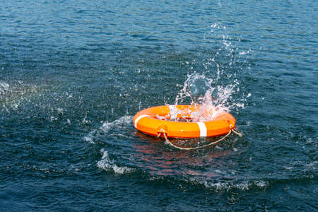 Orange lifebuoy in the sea on the water. The lifebuoy fell with a splash to the surface of the water, motion blur Banque d'images