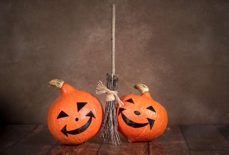 Two Halloween pumpkins and a witch's broom on a brown background Stockfoto