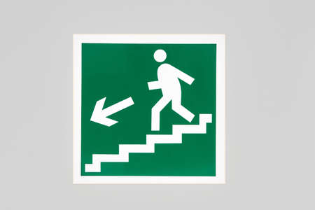 Exit sign during a fire with a graphic of a person and a ladder on the building wall