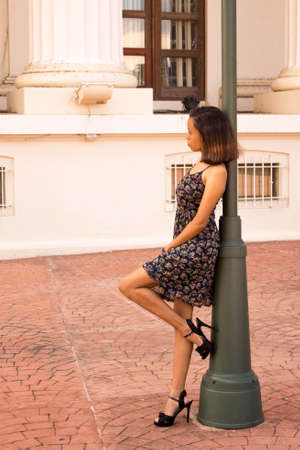 Woman leaning on the lamp post Stockfoto