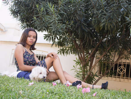 Woman sitting with her dog on the grass